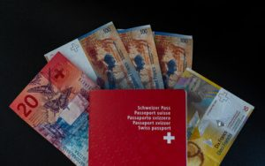 swiss passport in front of swiss banknotes